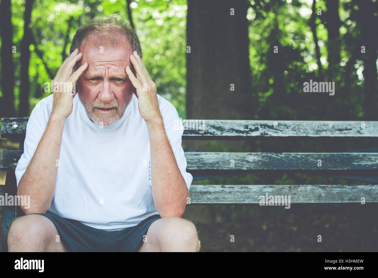 Closeup portrait, stressed older man in white shirt, hands on head with bad headache, sitting on bench - Stock Image