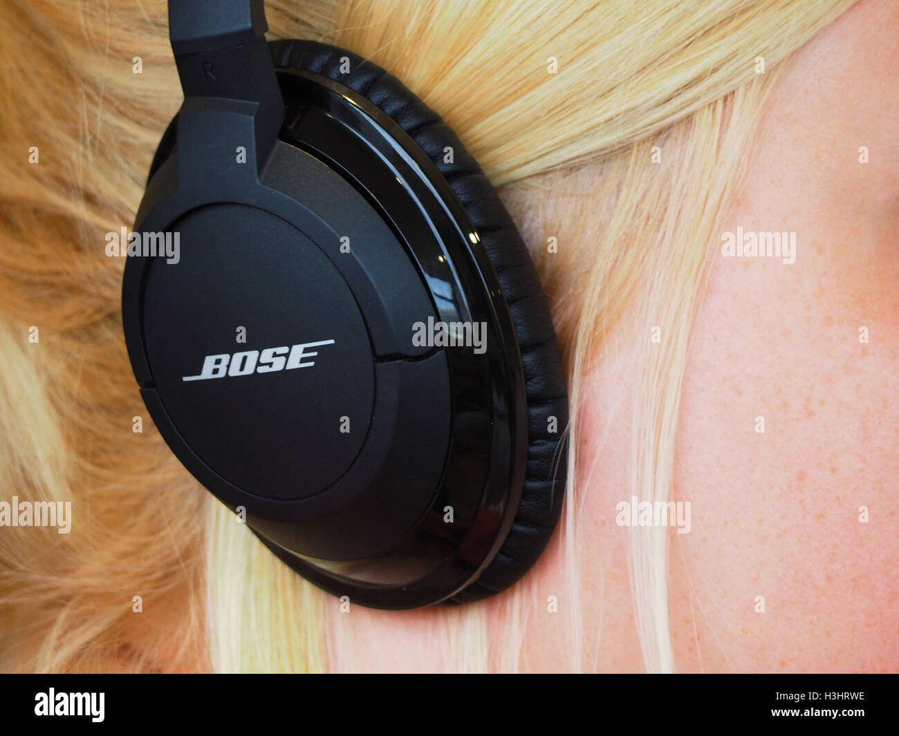 Bose headphones on a blond haired girl - Stock Image