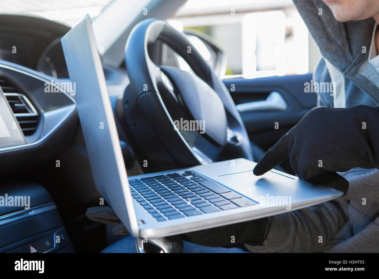 Thief Using Laptop To Hack Into Car Security Software - Stock Image