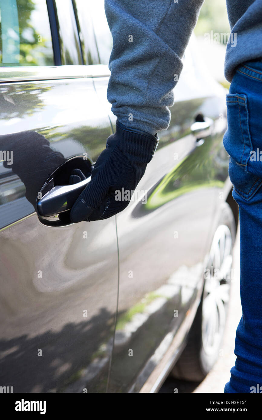 Car Thief Trying Door Handle To See If Vehicle Is Locked - Stock Image