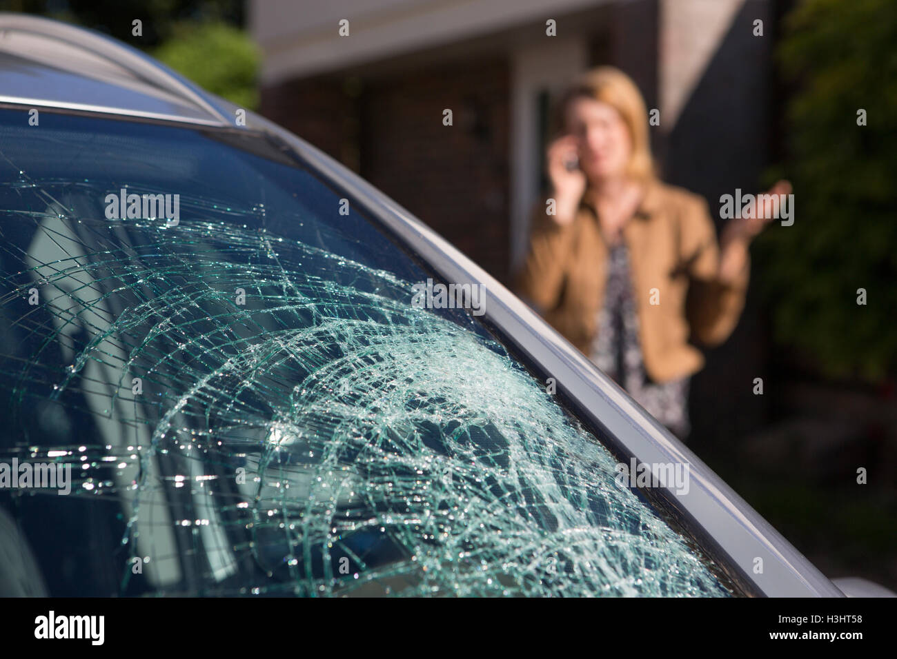 Woman Phoning For Help After Car Windshield Has Broken - Stock Image