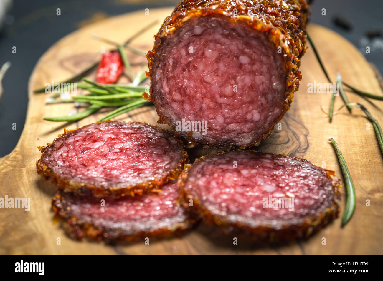 dried salami crusted in ground red pepper on dark background - Stock Image