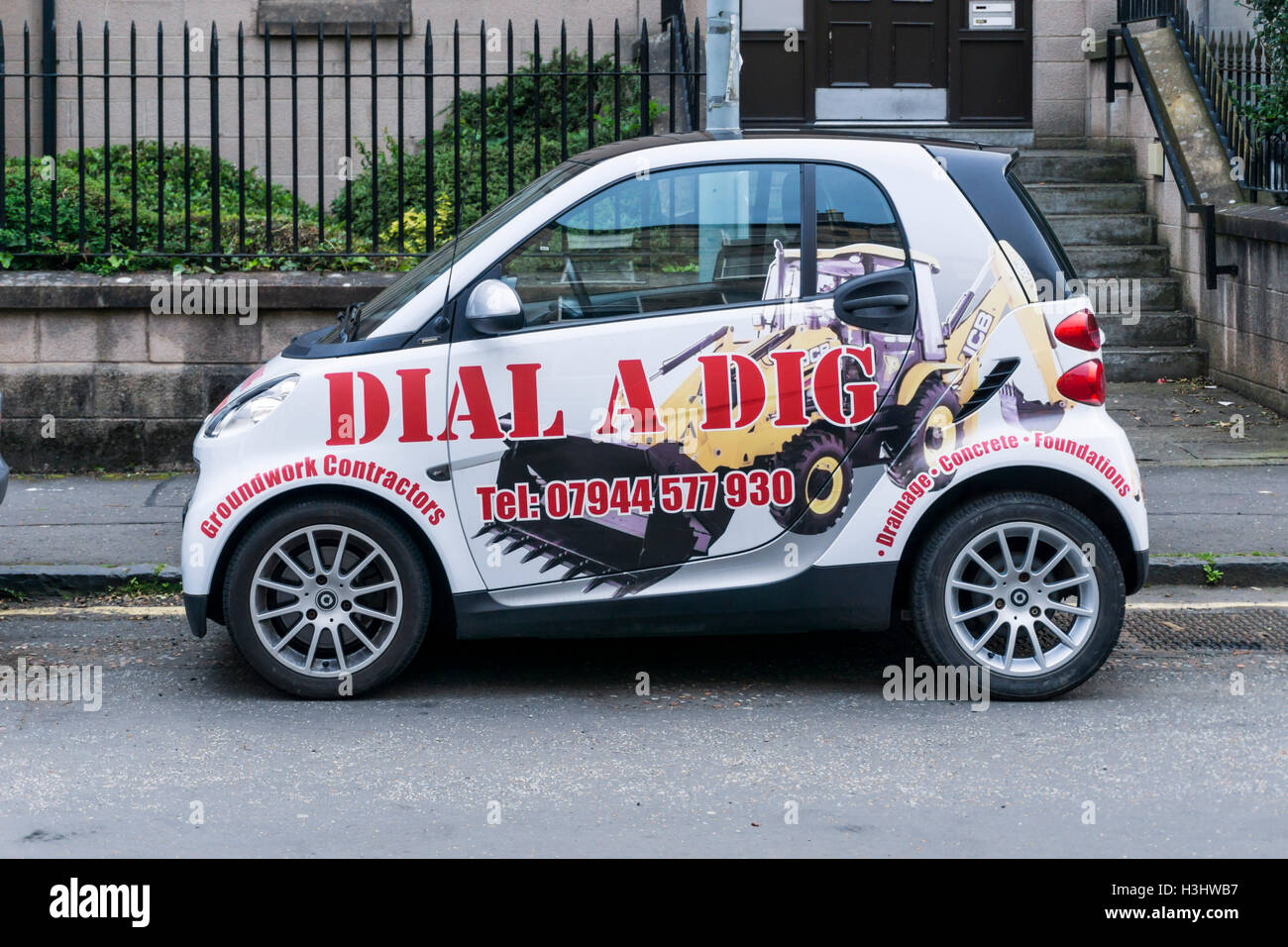 Advert for Dial a Dig groundwork contractors on the side of a Smart Fortwo car. - Stock Image