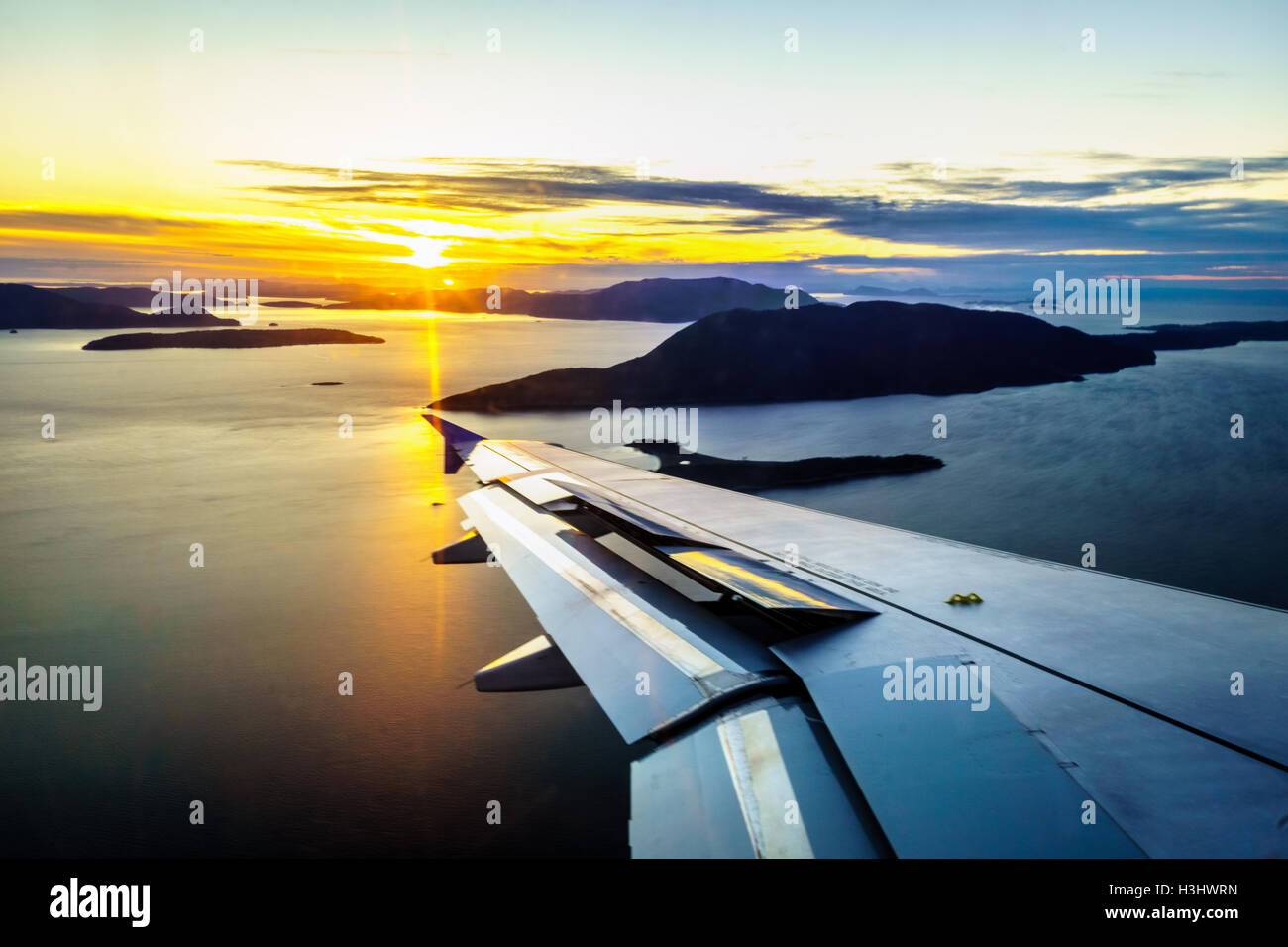 Sunset over Juan de Fuca Street and airplane wing of the coast of Bellingham in Washington State when preparing - Stock Image