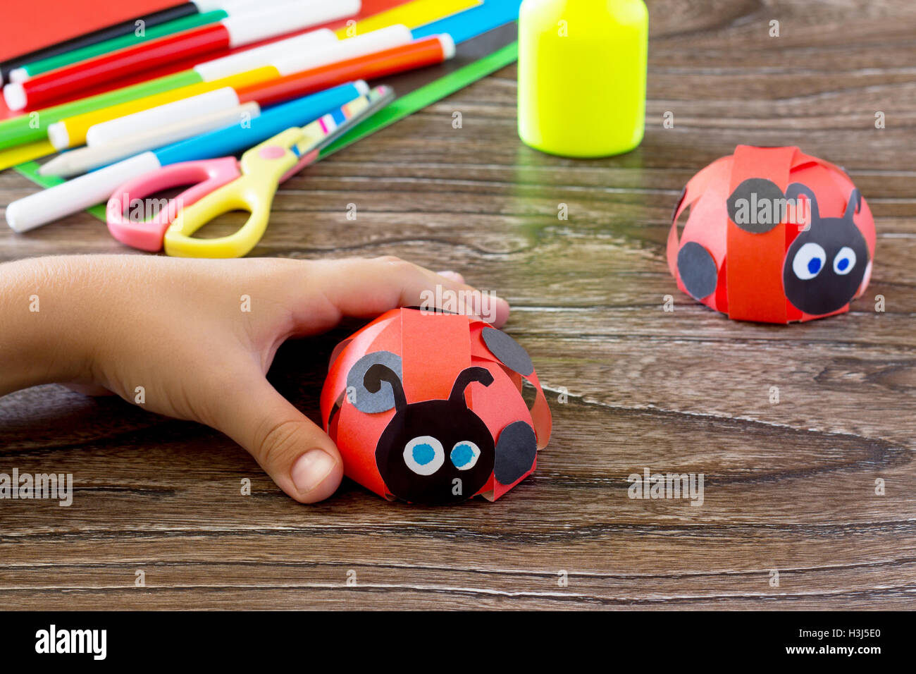 Colorful paper for children handmade odd job ladybug on a blue