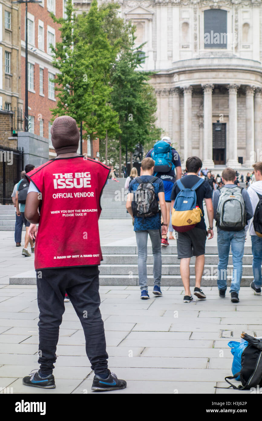 The Big Issue magazine official vendor in a red tabard outside St Paul's Cathedral, City of London, UK - Stock Image