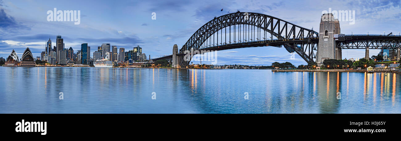WIde panorama of Sydney city landmarks across harbour from  house to Harbour bridge with CBD skyscrapers in between. - Stock Image