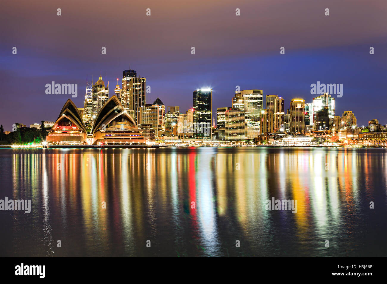 Sydney city CBD landmarks across harbour waters at sunrise brightly illuminated reflecting lights in blurred water. - Stock Image