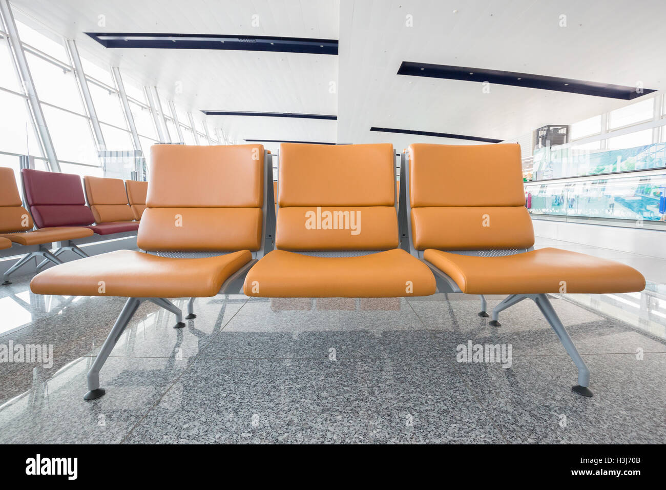 Close Focus On Three Leather Chairs In Orange Color Which Connected  Together As A Bench On Shiny Marble Floor In White Building