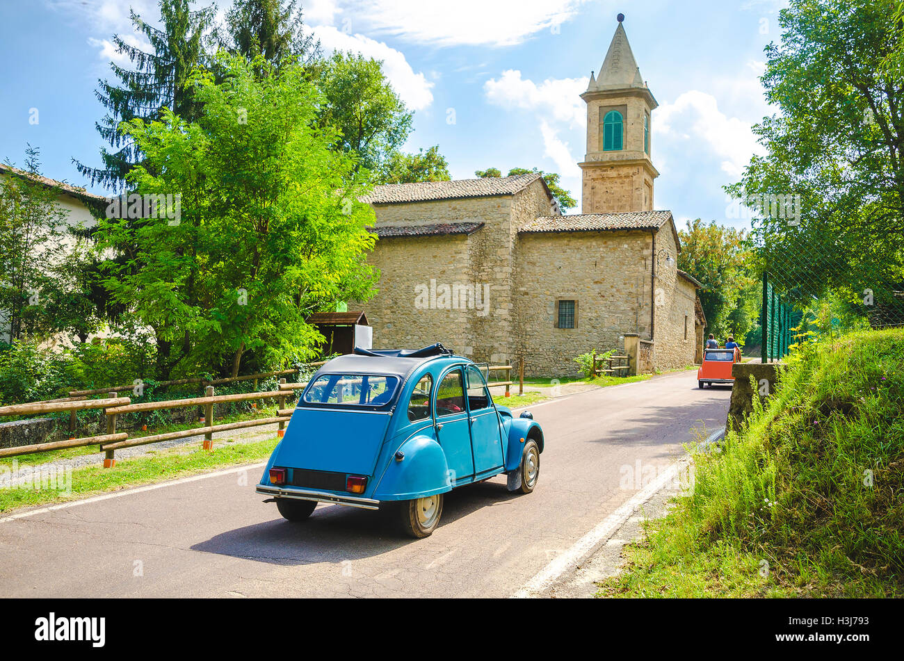italy road trip vintage car travel countryside church - Stock Image