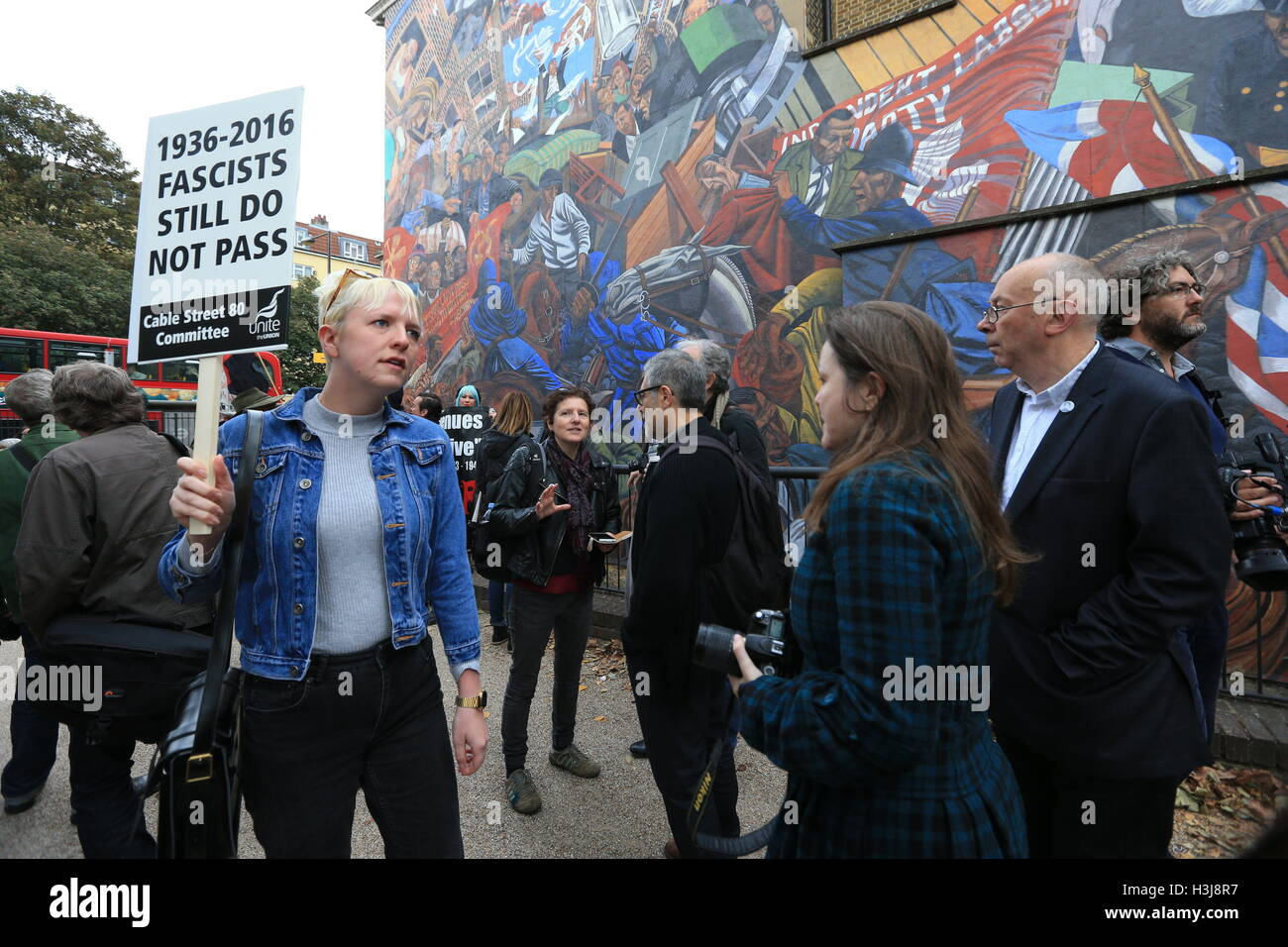 Demonstrators pass by a mural on Cable Street in the East End of London which commemorates the Battle of Cable Street. - Stock Image