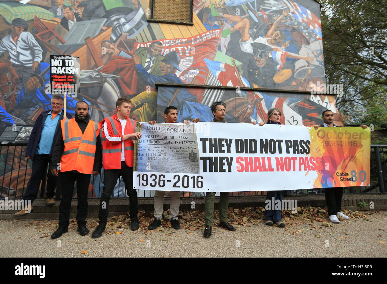 Demonstrators in front of a mural on Cable Street in the East End of London which commemorates the Battle of Cable - Stock Image