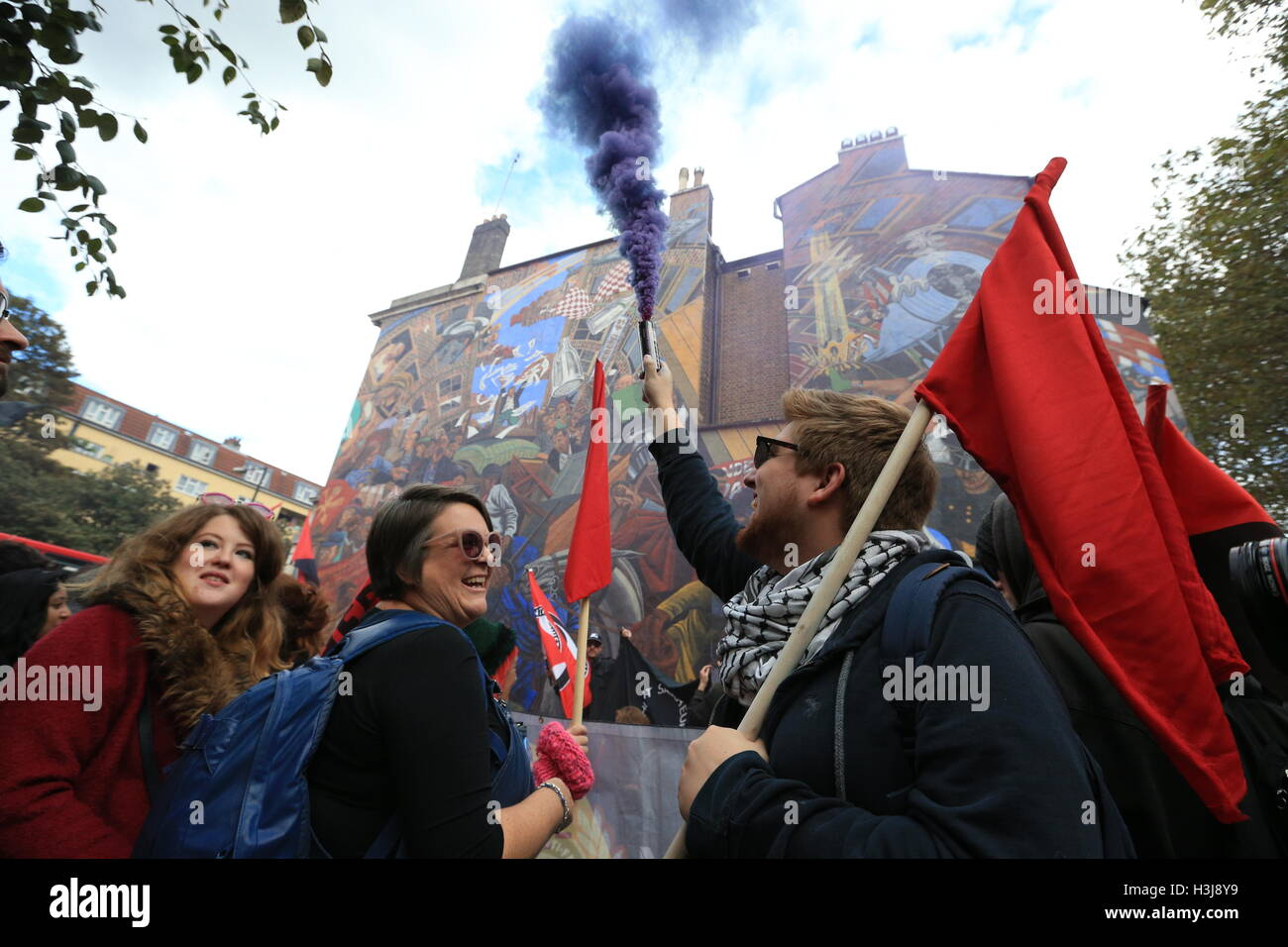 A demonstrator releases a smoke flare in front of a mural on Cable Street in the East End of London, which commemorates - Stock Image