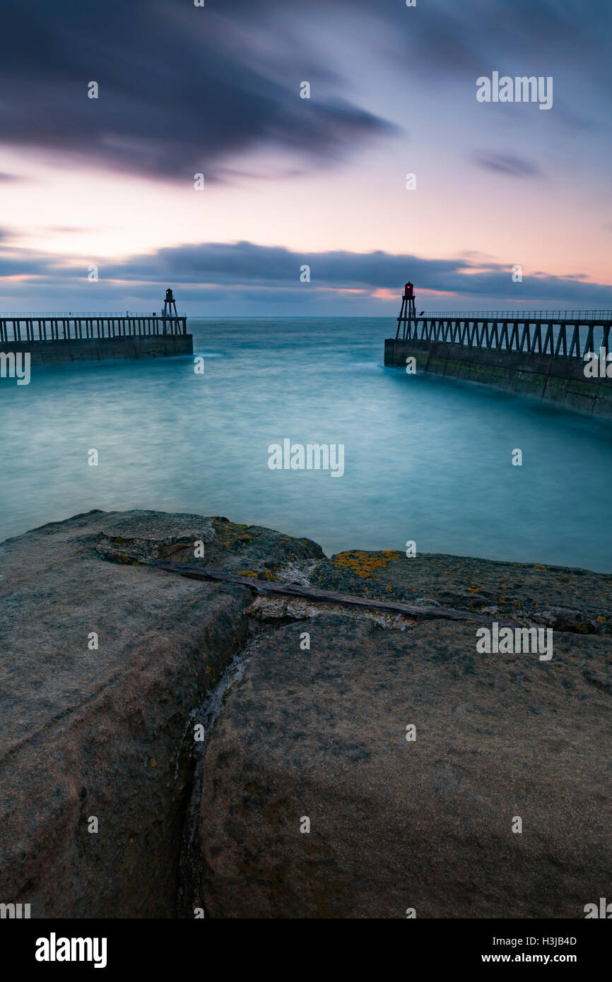 The breakwaters and pier at Whitby, North Yorkshire at sunset. Stock Photo