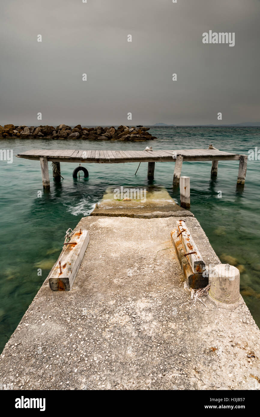 A damaged and dangerous jetty collapses into the sea in Greece as a storm cloud blows in. Stock Photo