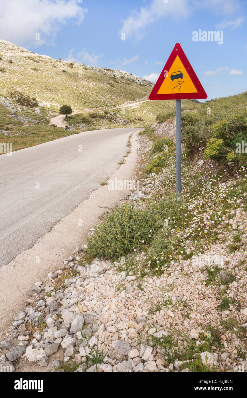 A Greek road sign showing a dangerous road, Greece. - Stock Image