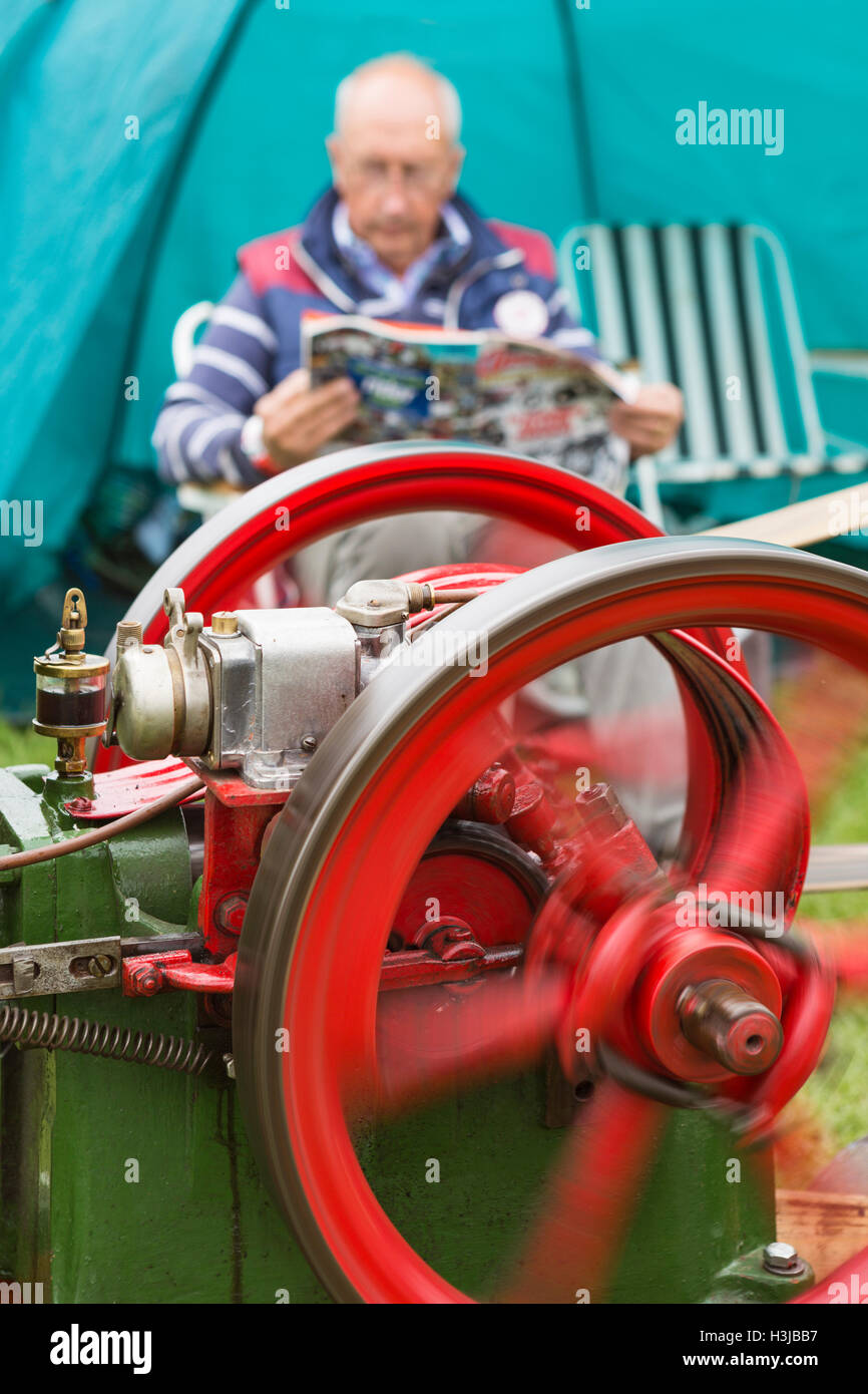 A Stationary Engine close up with the owner reading a magazine in the background. Stock Photo