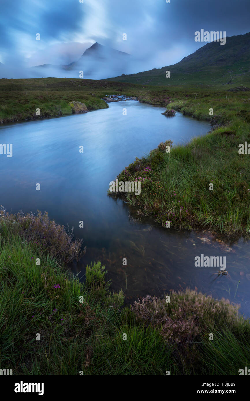 Nant Gwryd flows from Llyn Cwmffynnon in the cool blue dawn light. Crib Goch and the Snowdon Horseshoe is shrouded Stock Photo