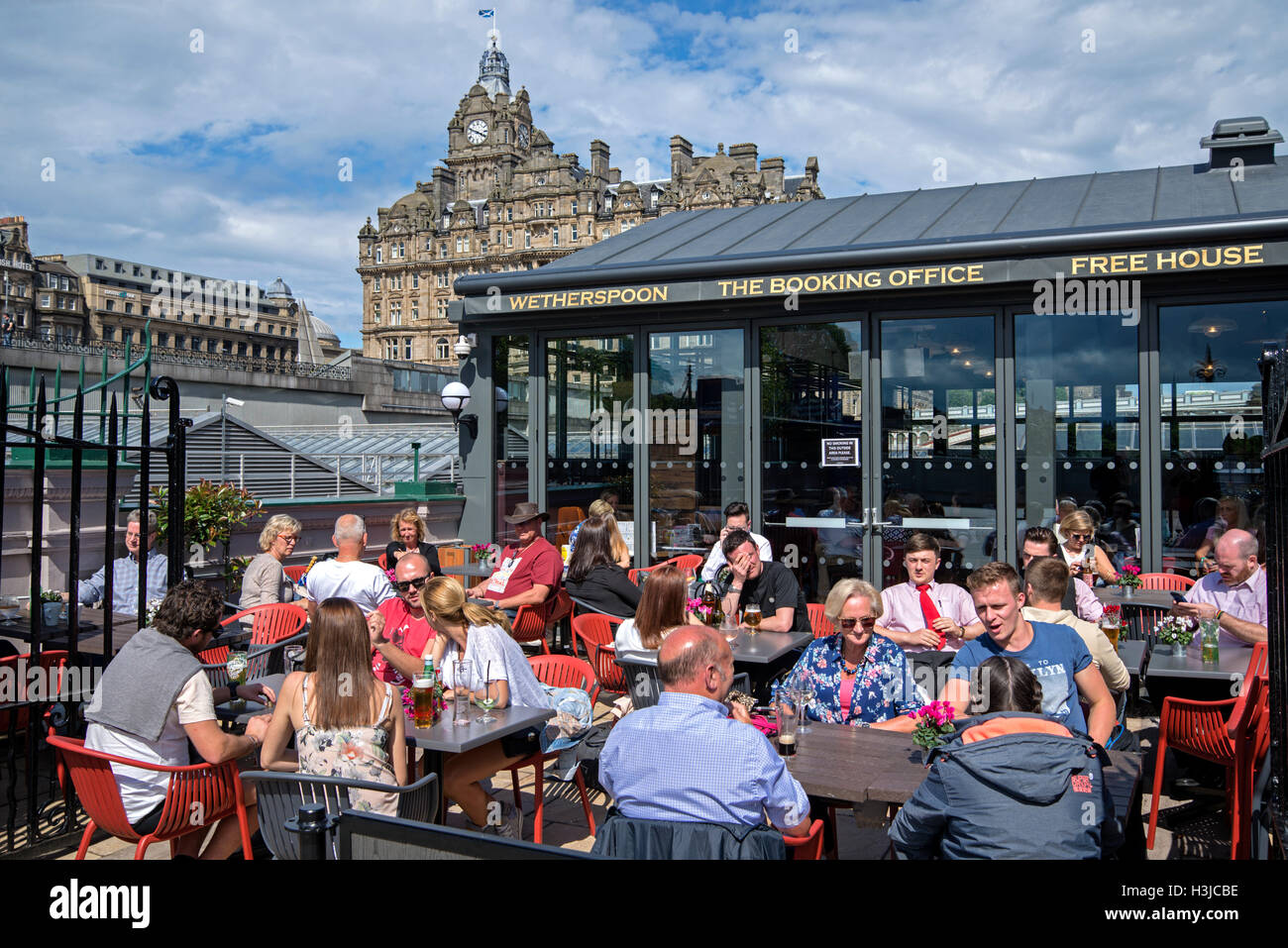 Customers enjoying a drink at Wetherspoon's on Waverley Bridge, Edinburgh with the Balmoral Hotel in the background. - Stock Image