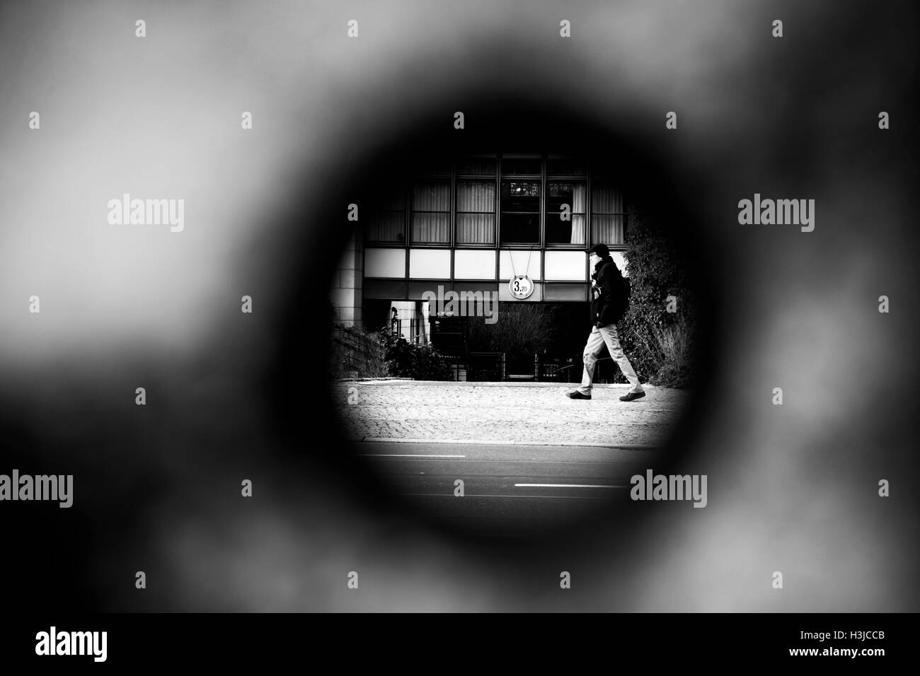 A view through a hole of the remaining Berlin Wall in Bernauer Strasse in the city. - Stock Image