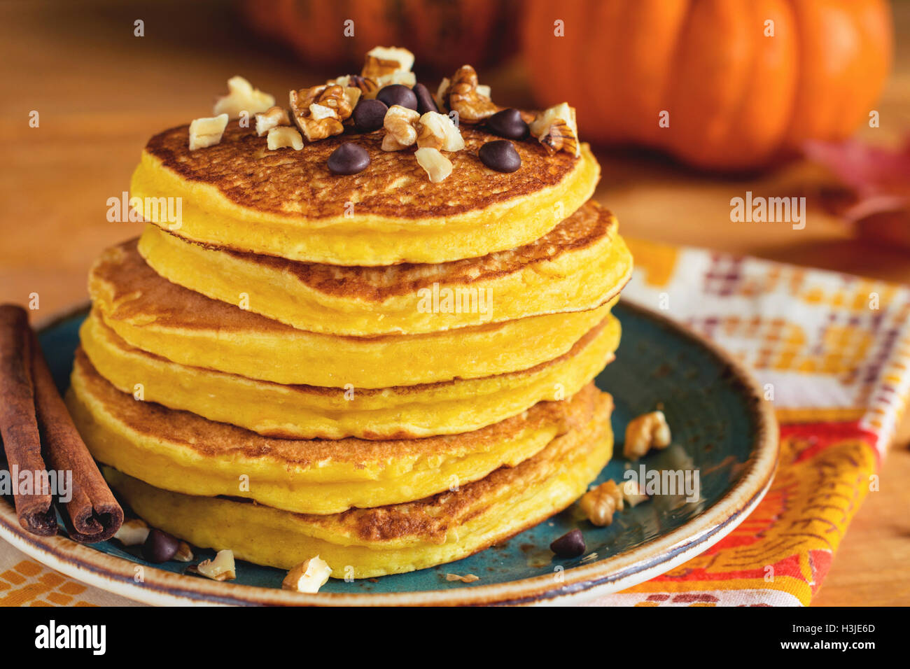 Pumpkin pancakes with nuts and chocolate on plate. Close up. Autumn breakfast meal, traditional American cuisine Stock Photo