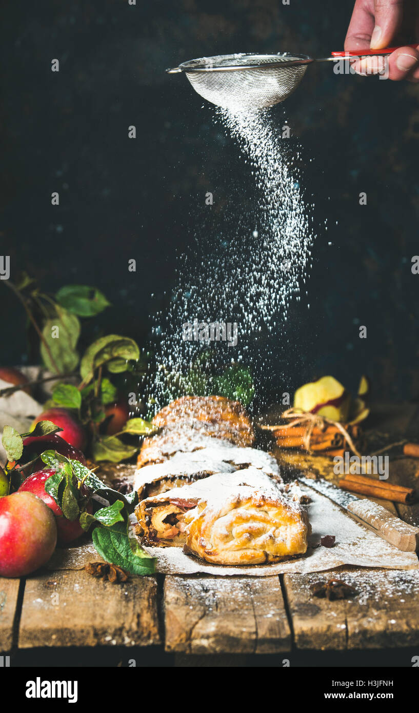Man's hand with sieve sprinkling sugar powder on apple strudel cake with cinnamon and fresh apples on rustic - Stock Image