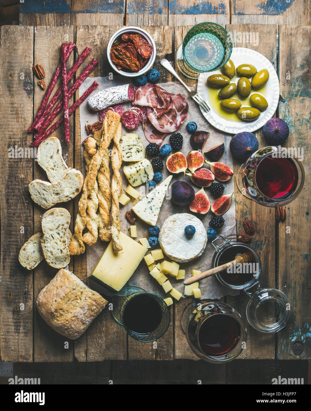 Wine and snack set with various wines in glasses, meat variety, bread, sun-dried tomatoes, honey, green olives, - Stock Image