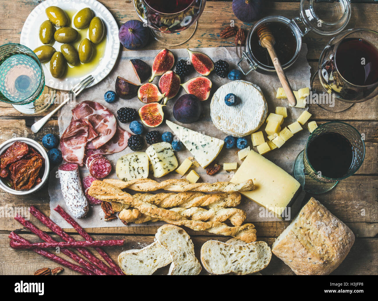 Wine and snack set with various wines in glasses, meat variety, ciabatta, sun-dried tomatoes, honey, green olives, - Stock Image