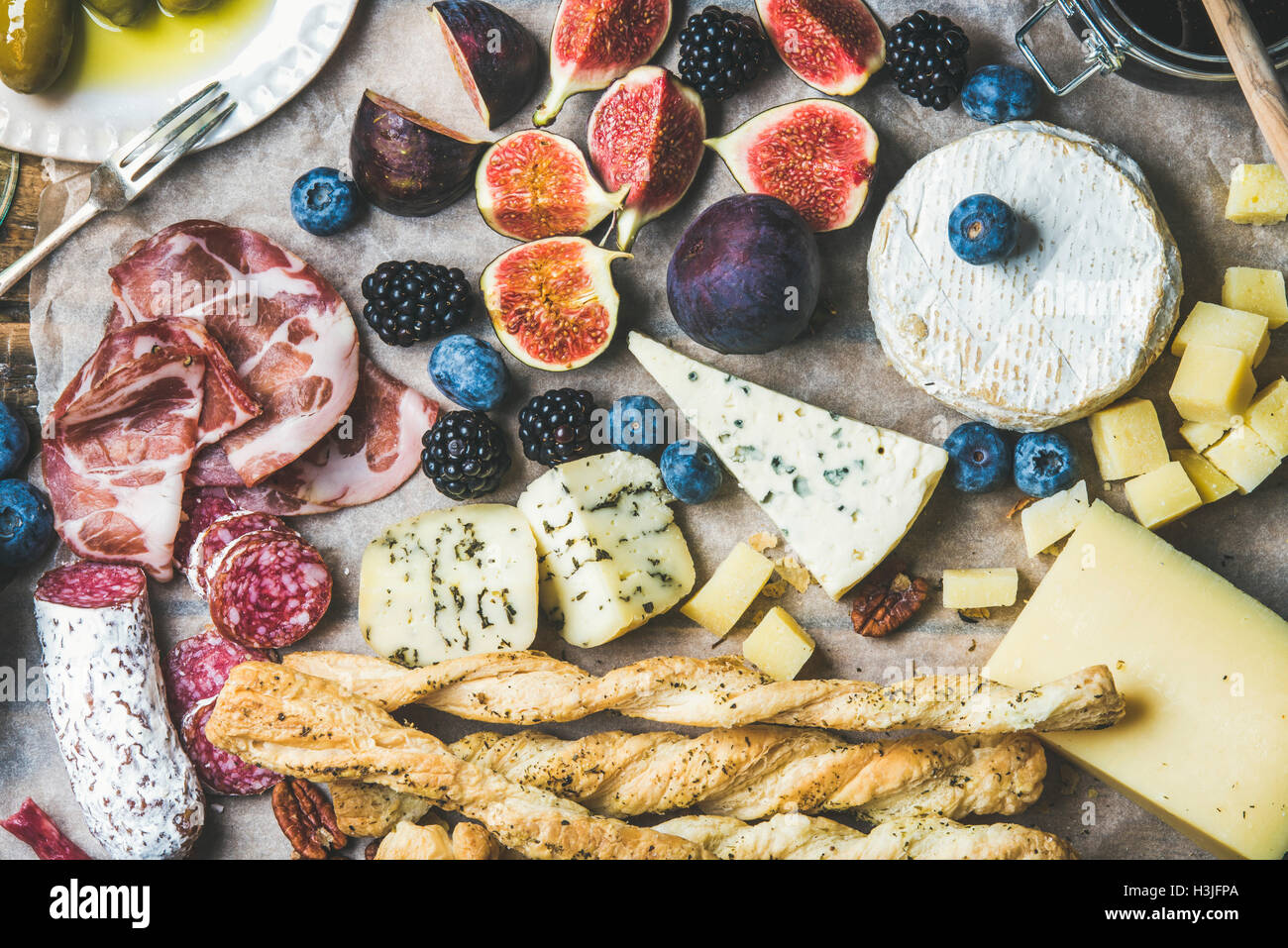 Close-up of wine snack set with meat variety, bread, green olives, figs, nuts and berries on wax paper, top view, - Stock Image
