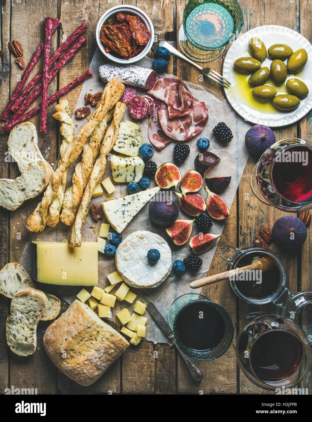 Wine and snack set with various wines in glasses, meat variety, bread, green olives, sun-dried tomatoes, figs, nuts - Stock Image