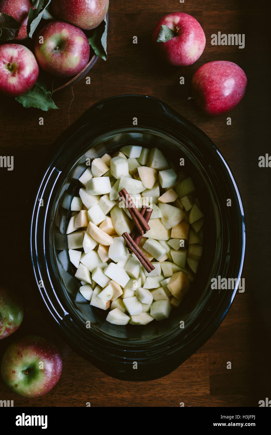 Sliced and peeled apples are placed in the bowl of a slow cooker - photographed from the top view. - Stock Image