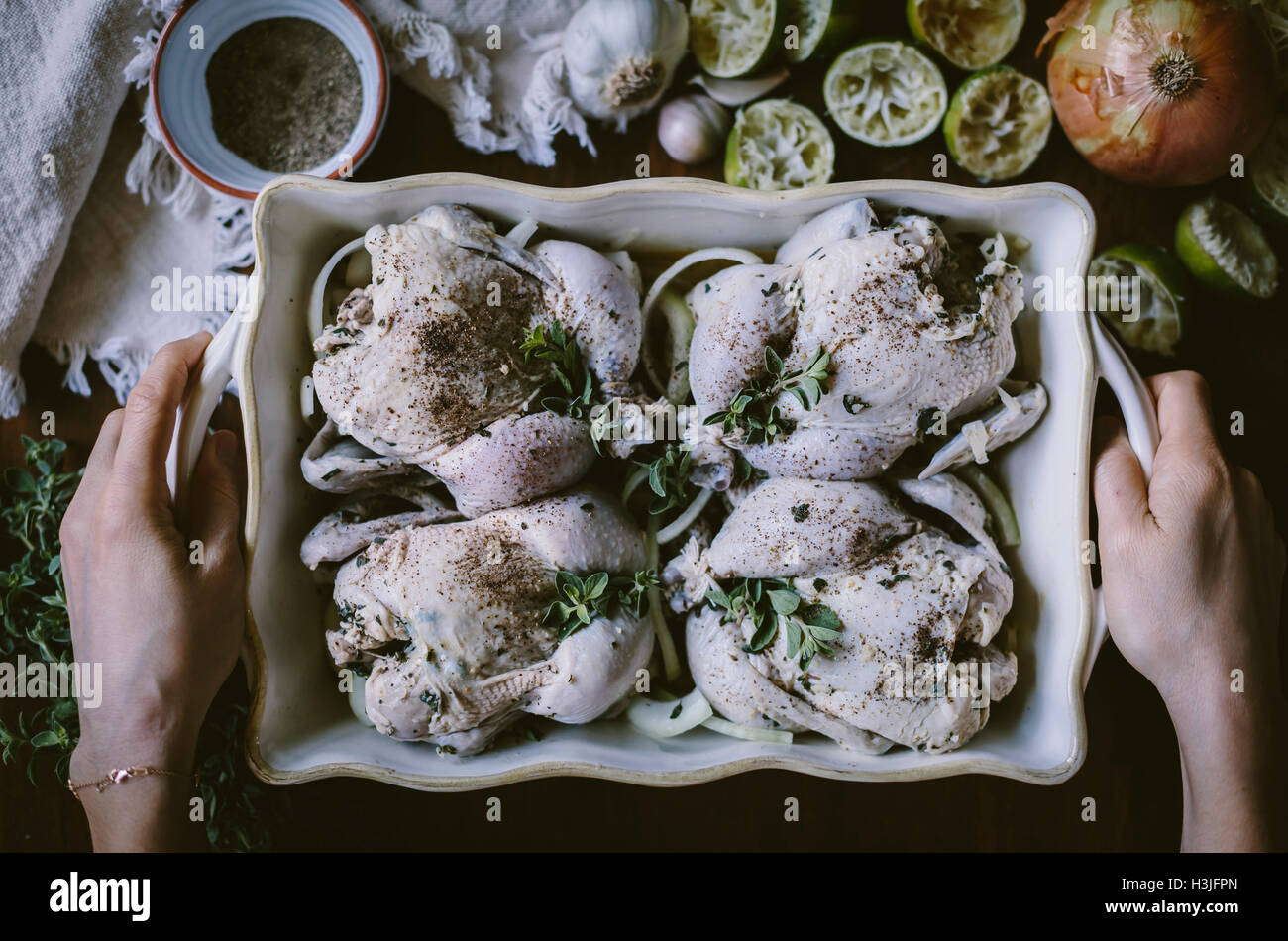 4 seasoned game hens are placed in a casserole pan are about to be placed in the oven. Stock Photo