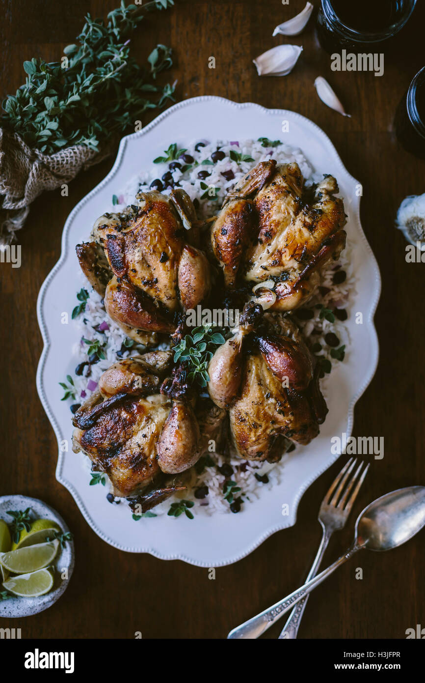 4 Cuban Roasted Game Hens are served on Cuban black bean rice and photographed from the top view. (higher view) - Stock Image