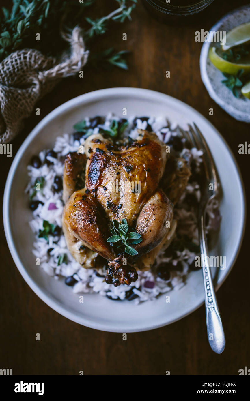 A Cuban Roasted game hen served on black bean rice is photographed from the top view. - Stock Image