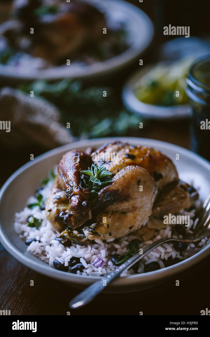 One roasted game hen served on top of black bean rice is photographed from the front view - Stock Image