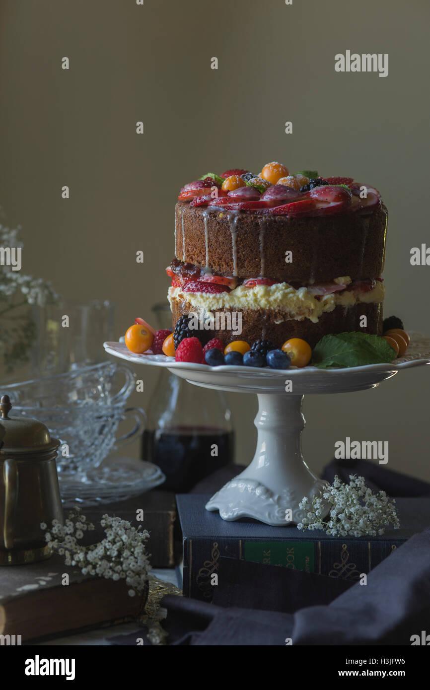 Vanilla cake decorated with fresh fruit. - Stock Image