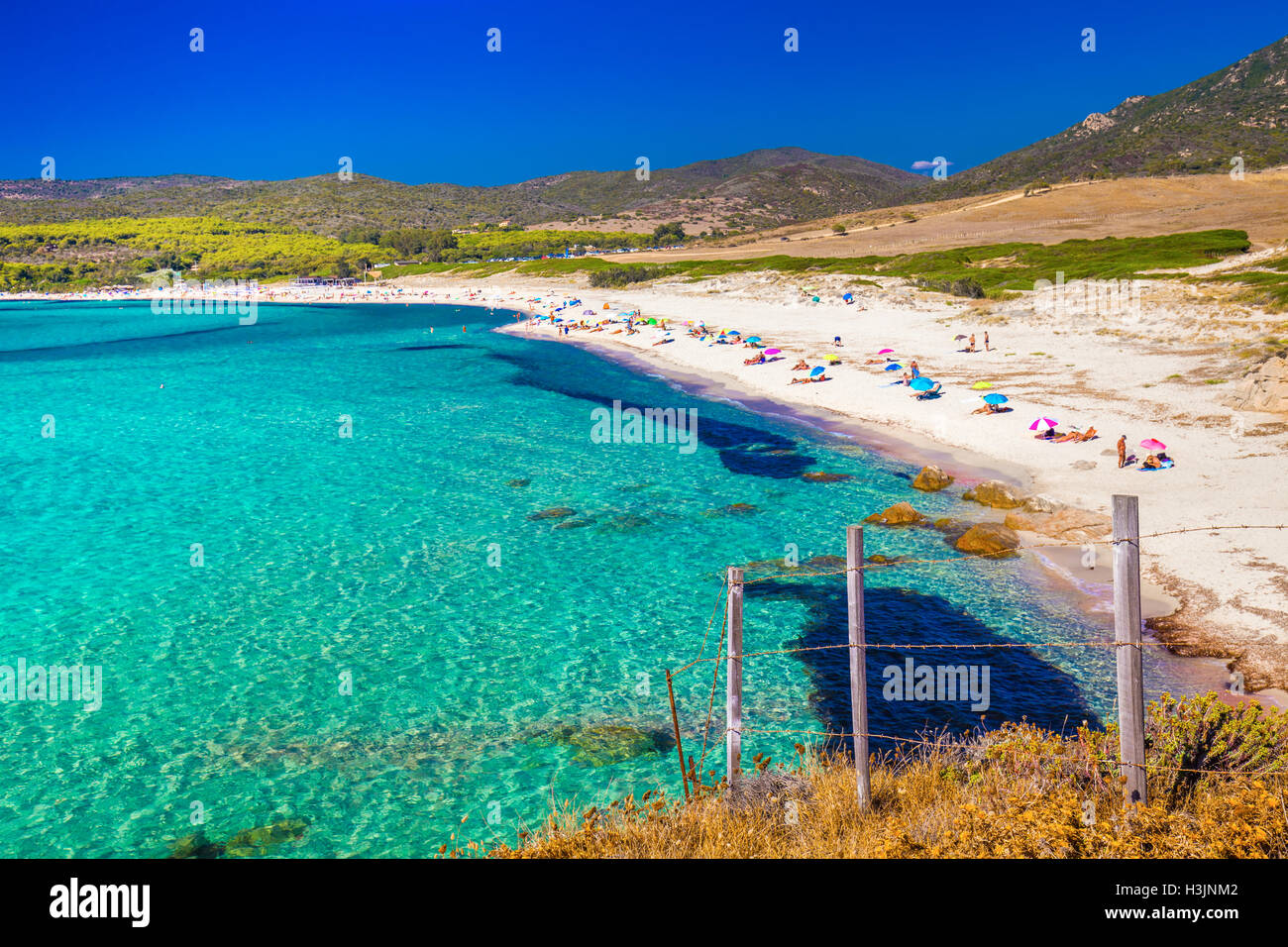 People enjoying the sunny weather on sandy Grand Capo beach with red rocks near Ajaccio, Corsica, Europe. Stock Photo