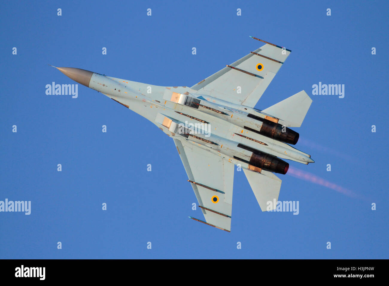 Military aviation. Underside view of a Ukraine Air Force Sukhoi Su-27 Flanker fighter jet plane flying with afterburners - Stock Image
