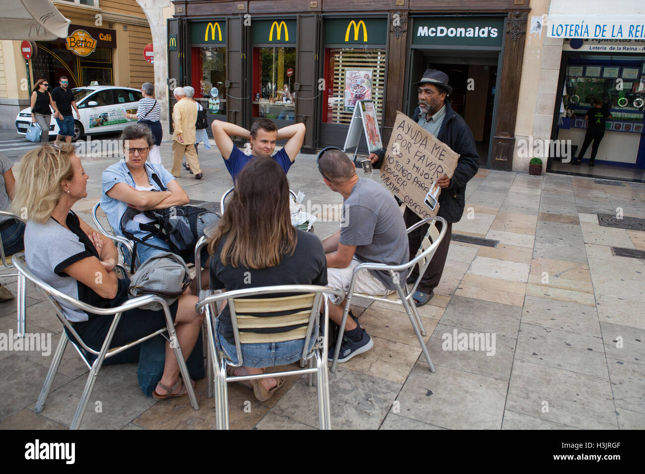 A beggar asks tourists for money outside a McDonalds restaurant in the old quarter of Valencia - Stock Image