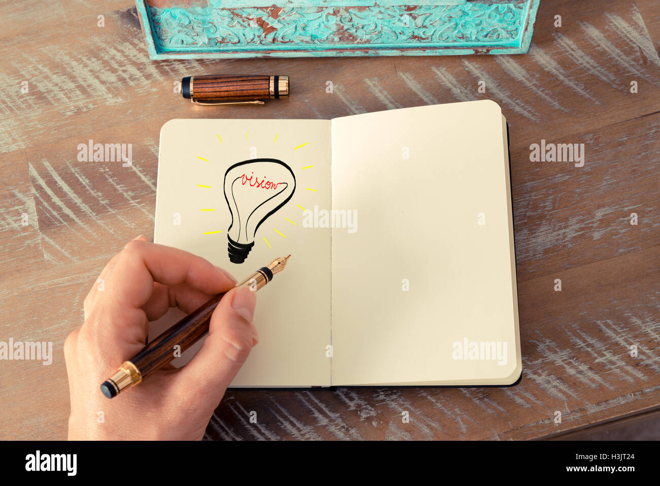 Retro effect and toned image of a woman drawing a lighting bulb with fountain pen on a notebook. VISION symbol and - Stock Image