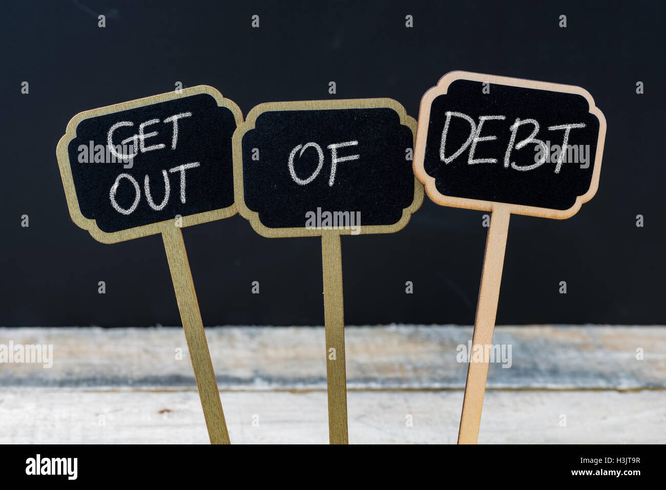 Business message GET OUT OF DEBT written with chalk on wooden mini blackboard labels - Stock Image