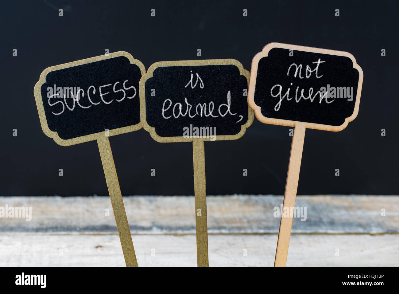 Business message SUCCESS IS EARNED, NOT GIVEN written with chalk on wooden mini blackboard labels - Stock Image