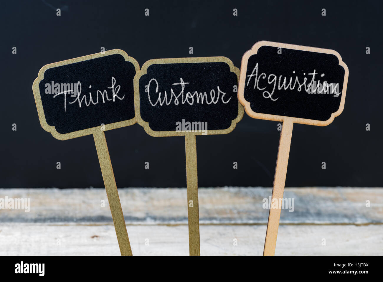 Business message THINK CUSTOMER ACQUISITION written with chalk on wooden mini blackboard labels - Stock Image