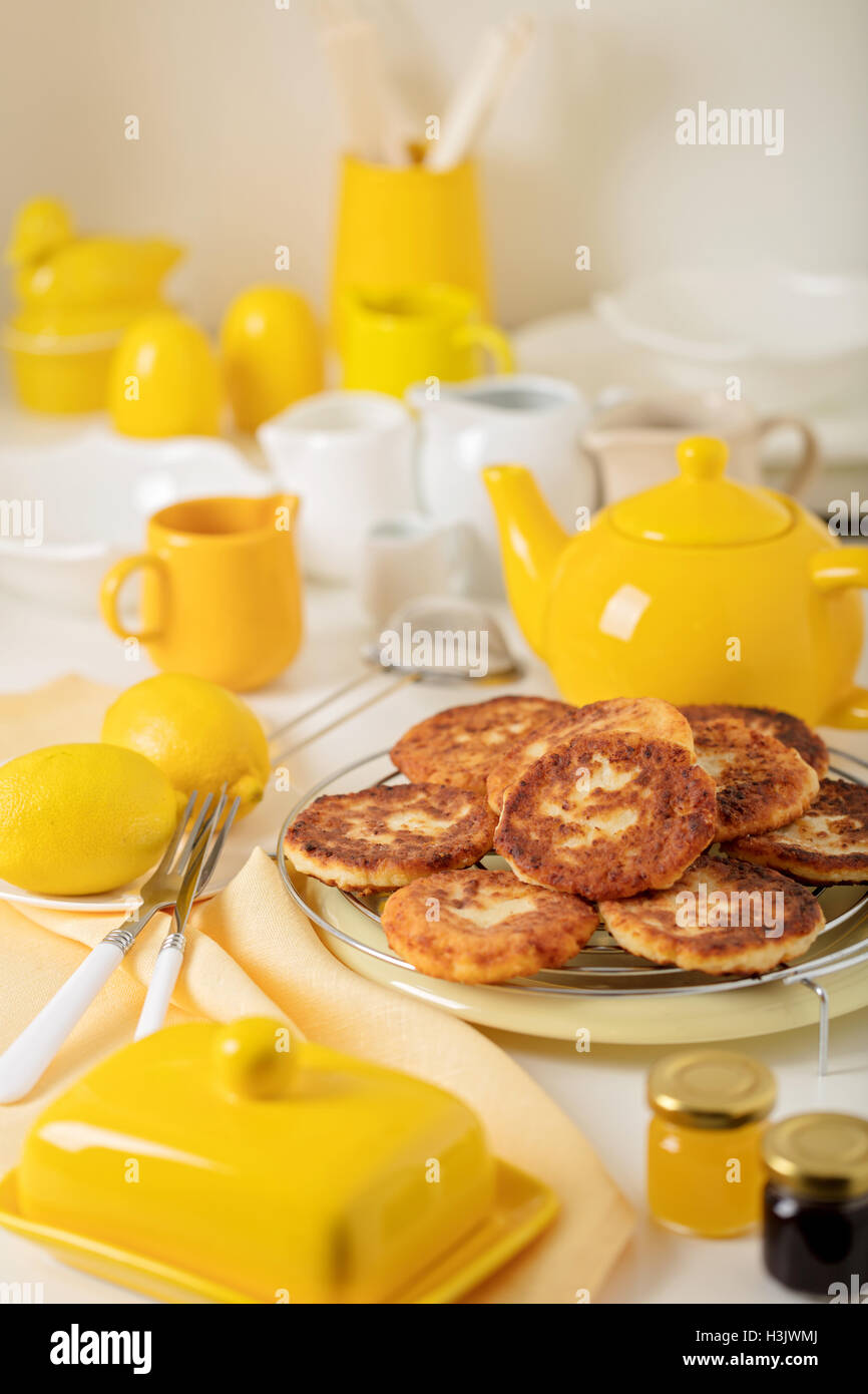 Breakfast. Cottage cheese pancakes with tea and lemon. Selective focus. - Stock Image