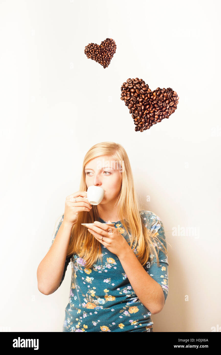 blond teenager girl drinking coffee and heart shaped coffee above her, love for coffee concept - Stock Image