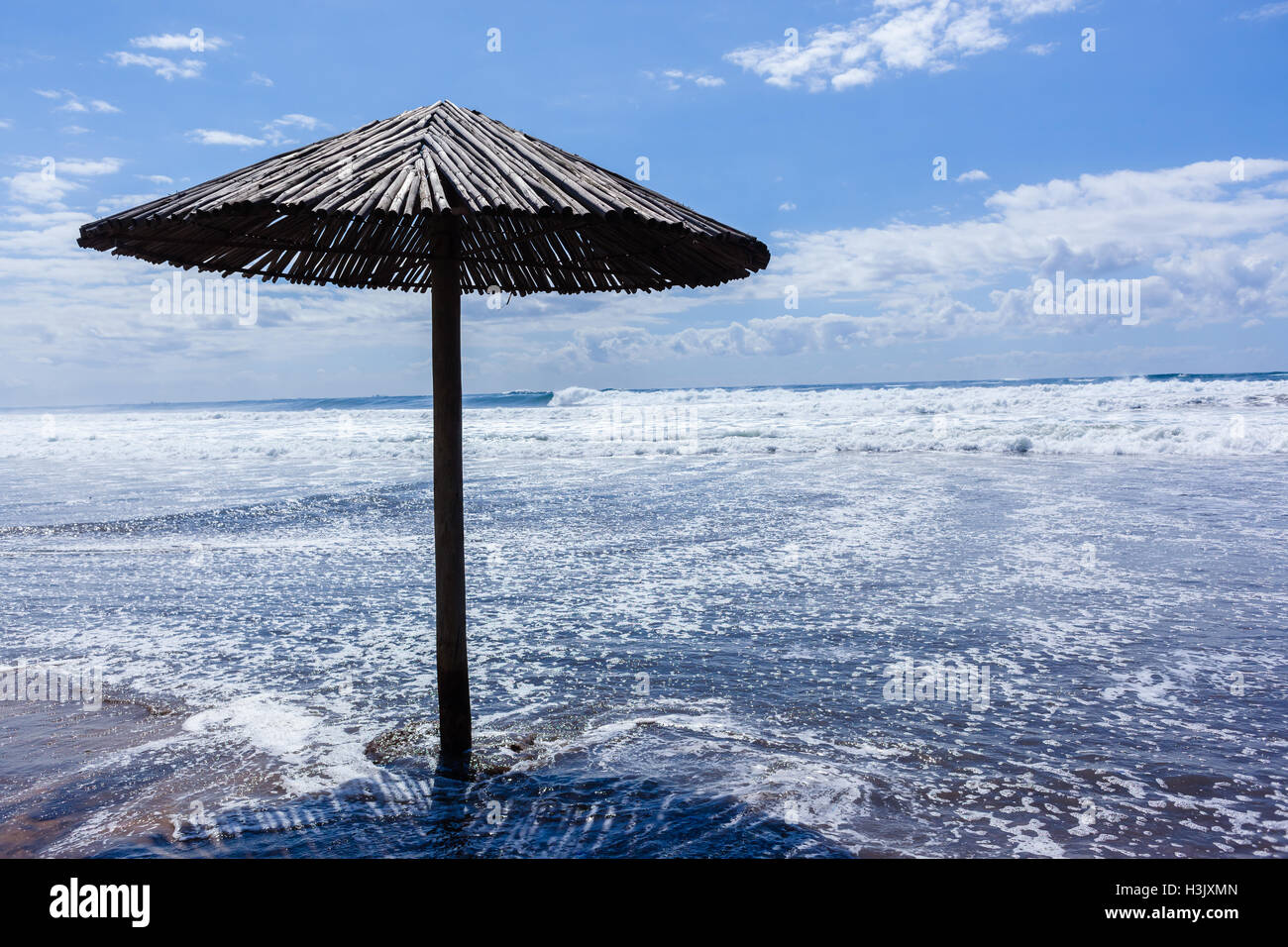 Beach umbrella on sands covered by sea water wash from ocean storm wave conditions. - Stock Image