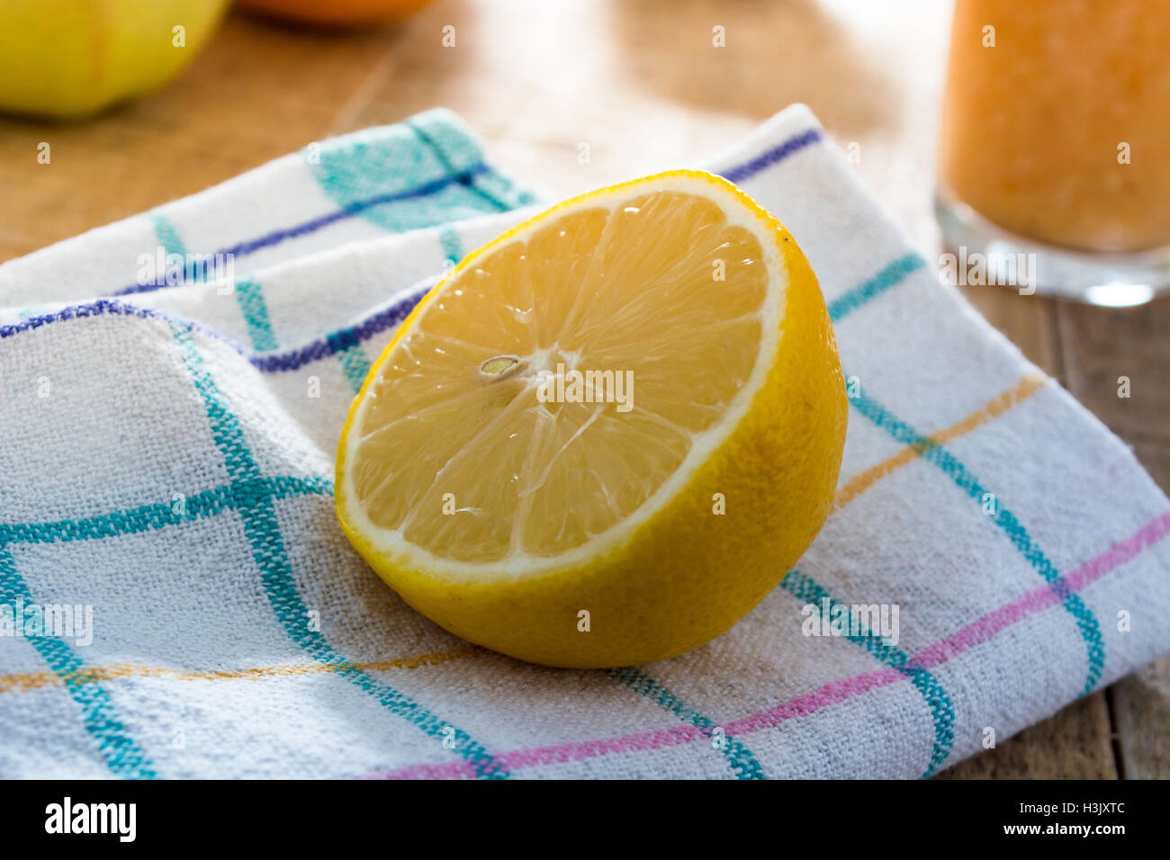 Lonely lemon on a kitchen cloth surrounded with other kitchen things - Stock Image