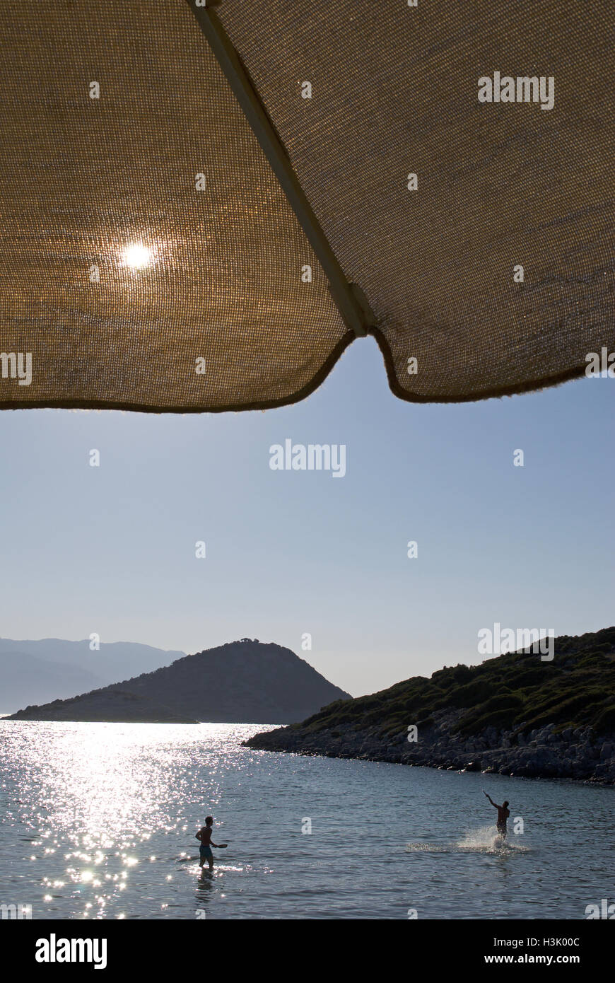 The sun shines through the parasol fabric on a hot summer's day in Samos, Greece. - Stock Image