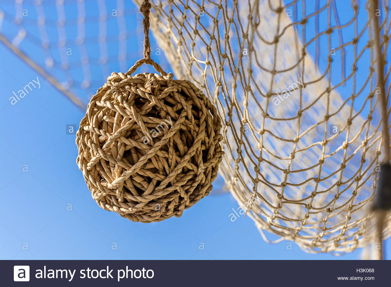 Fishing net and a wicker ball hanging, at background blue mediterranean sea on a a sunny day - Stock Image