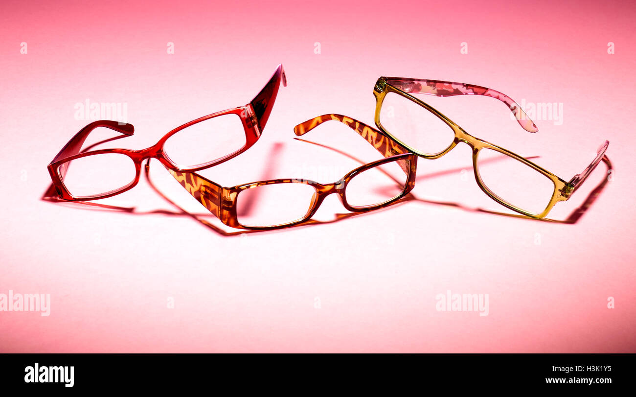 Three pairs of glasses on a pink background - Stock Image